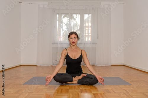 Attractive woman meditating alone in a room
