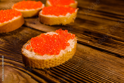 Sandwiches with red caviar on wooden table
