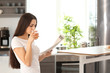 Young woman reading newspaper while drinking juice in kitchen
