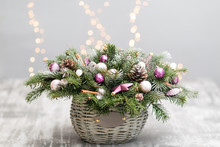Christmas Or New Year Greeting Card With A Wicker Basket With Pine Cones, Fir Branches, Decorative Balls On Old Wooden Background. Vintage Style, Selective Focus. On The Background Lights Garland