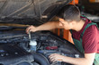 Male mechanic checking level of oil in car engine