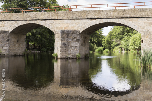 Staande foto Brug Old stone bridge for a road that crosses a small dam of a river