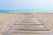 Wooden Boardwalk At Beach In Sand And Sea In The Background