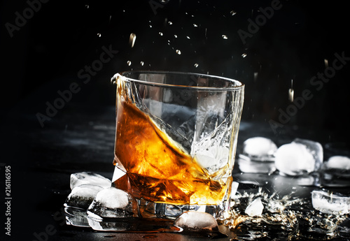 Whiskey with ice, splashes out of glass, dark background, selective focus