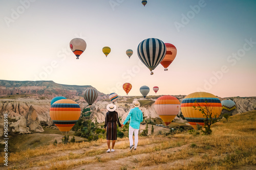 Fotografie, Obraz  happy young couple during sunrise watching the hot air balloons of Kapadokya Cap