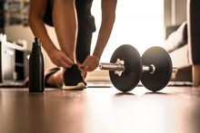 Morning Workout Routine In Home Gym. Fitness Motivation And Muscle Training Concept. Man In Sneakers Tying Shoelaces In Sunlight. Athlete Starting Exercise With Dubbell Weight.