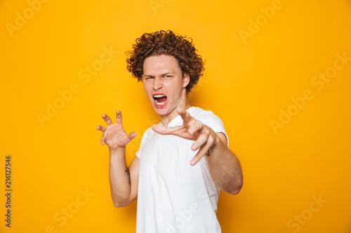 Valokuva  Photo of aggressive man 20s in casual t-shirt screaming and gesturing at camera,