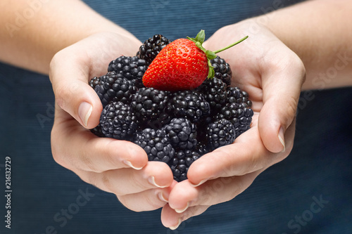 closeup of woman hands holding berries at home.