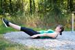 Glückliche junge Frau macht Fitness Übungen im Park oder Wald
