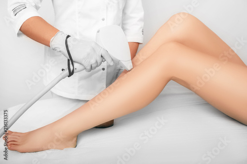 Valokuvatapetti beautician removes hair on beautiful female legs using a laser