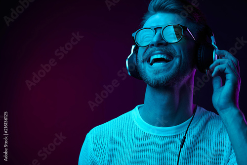 Photographie Neon portrait of bearded smiling man in headphones, sunglasses, white t-shirt