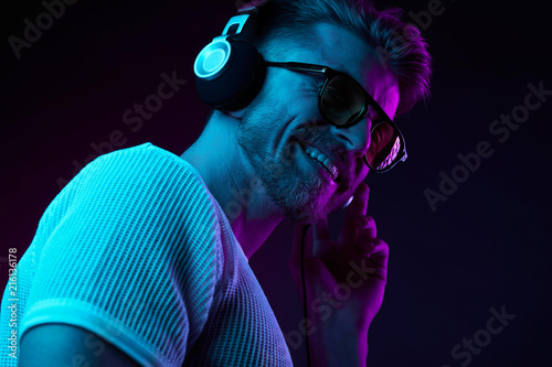 Neon light portrait of bearded smiling man in headphones, sunglasses, white t-shirt. Listening to music - 216136178