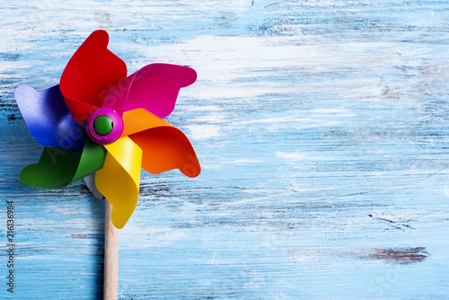 Fotografie, Tablou  colorful pinwheel on a blue wooden surface