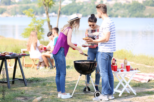 Young people having barbecue party on sunny day outdoors