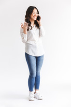 Full Length Photo Of Joyous Chinese Woman With Long Dark Hair Holding And Talking On Mobile Phone, Isolated Over White Background In Studio