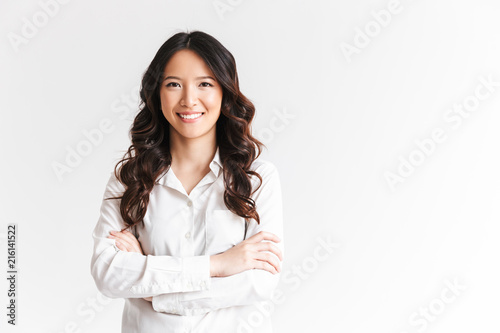 Fototapeta Portrait of gorgeous asian woman with long dark hair looking at camera with beautiful smile and arms crossed, isolated over white background in studio obraz