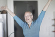 Smiling woman standing in her living room with her arms in the air