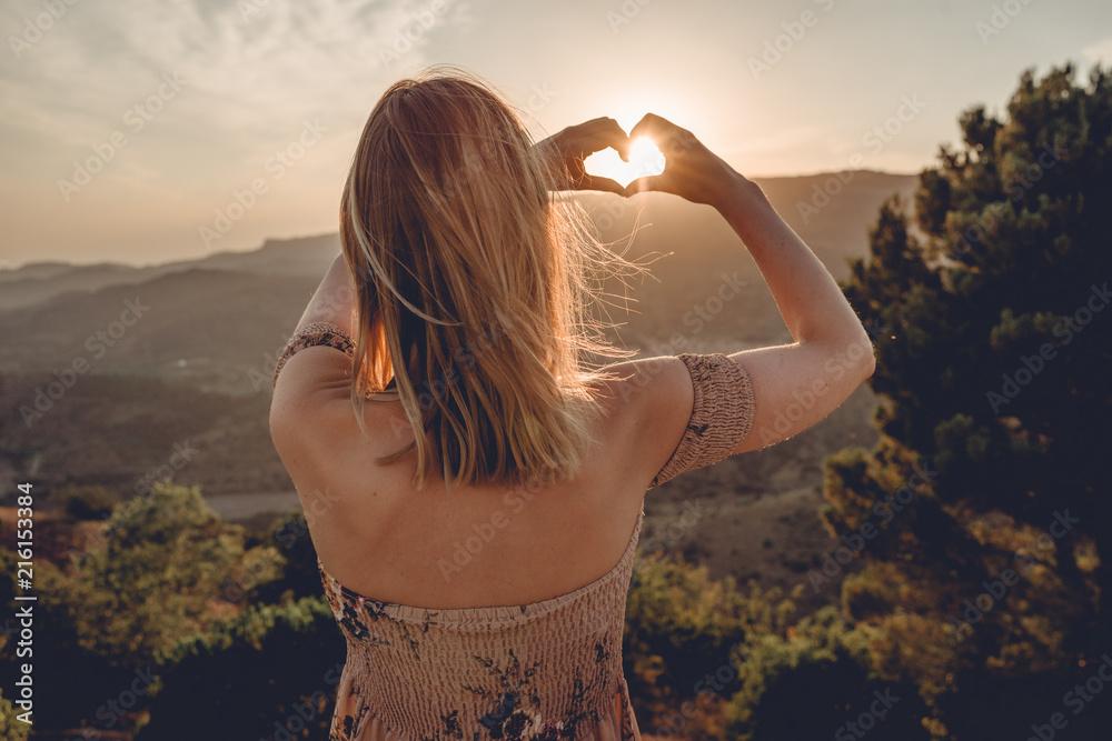 Fototapeta Frau beim Sonnenuntegang mit Herz