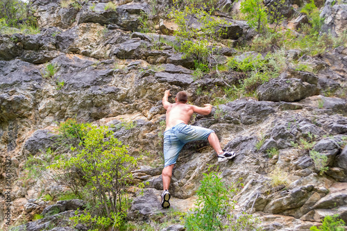 Poster  Young man climber in jeans shirts and bare torso climbs on rocks to the top in m