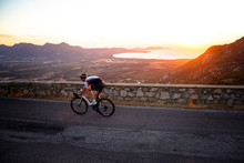 Man Cycling On Mountain Road At Sunset, Corsica, France