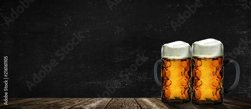 Montage in der Fensternische Bier / Apfelwein Zwei Bierkrüge vor schwarzem Hintergrund