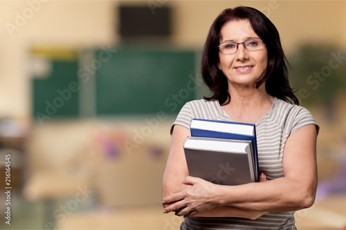 Carta da parati Mature woman teacher with books on background