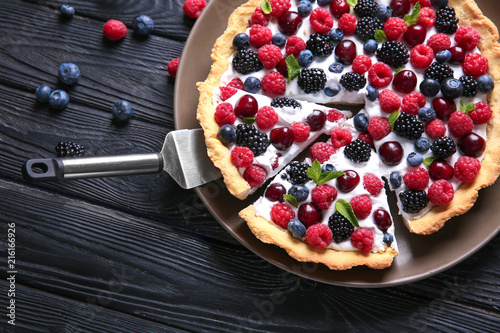 Obraz na płótnie Plate with delicious berry pie on wooden background, top view