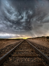 Supercell Rotates At Sunset Over Infinite Stretch Of Train Tracks, Arriba, Colorado, US
