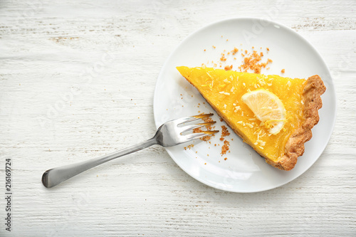 Foto Plate with piece of tasty lemon pie on white wooden table