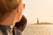 Tourists Looking At Statue Of Liberty Silhouette In Sunset From The Staten Island Ferry, New York City, USA.
