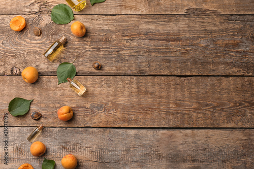 Composition with fresh apricots and essential oil on wooden table - 216170936