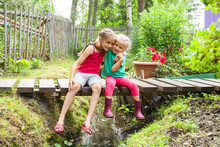 Happy Smiling Children Sit On The Bridge At The Creek Embracing One Another In A Garden. Kids Playing Outdoors In Summer