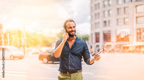 Foto  Middle Age Hipster Man Communicating Outdoors on Street Holding Sunglasses Smili