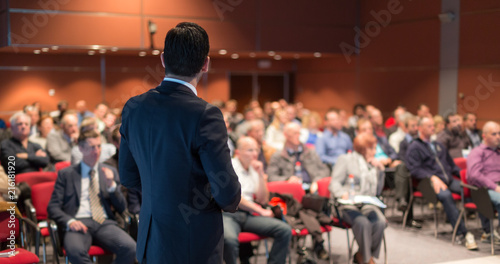 Fototapeta Speaker giving a talk on corporate business conference. Unrecognizable people in audience at conference hall. Business and Entrepreneurship event. obraz na płótnie