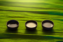 Three Cups Of Ceramics On The Green Background