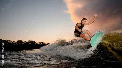 Handsome muscular young man wakesurfing down the river waves