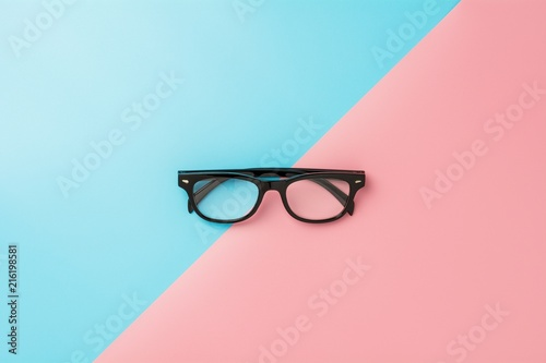 Fotografia black glasses on blue and pink background.