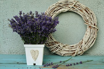 Fototapeta Lawenda A bouquet of fresh lavender in a white pot with a heart and a wicker wreath in a vintage style.