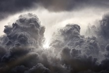 Sun Rays Breaking Through The Dark Clouds. Clouds Background. Dramatic Grey Clouds