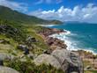 beautiful paradise beach with green grass, turquoise water and granite rocks at the Guarda do Embaú beach, Santa Catarina, Brazil