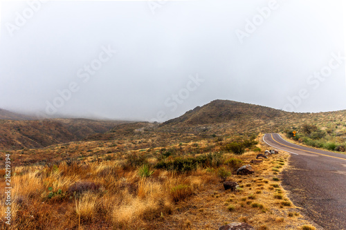 Poster Wit desert landscape covered in clouds with a road winding through the hills