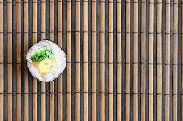 Sushi roll lie on a bamboo straw serwing mat. Traditional Asian food. Top view. Flat lay minimalism shot with copy space