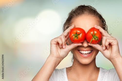 Beautiful laughing woman holding two ripe tomatoes Fototapete
