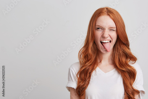 Portrait of cheerful playful young woman with long wavy red hair and freckles we Fototapeta