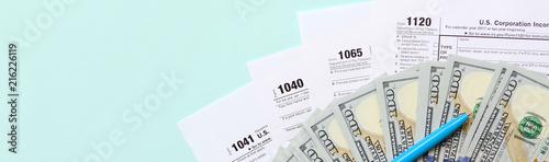 Cuadros en Lienzo Tax forms lies near hundred dollar bills and blue pen on a light blue background