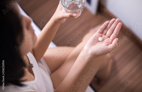 Obraz Woman with white pill painkillers on hand and a glass of water - fototapety do salonu