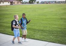 Two Diverse School Kids Walking Home Together After School And Talking Together. Back To School Photo Of  Diverse School Children Wearing Backpacks In The School Yard