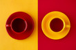 Tea in cups on different backgrounds. Yellow and red cups of tea pairs on yellow and red backgrounds. View from above. Contrast of different colors.