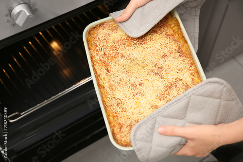 Woman taking baking dish with spinach lasagna out of oven