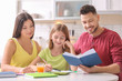 Little girl doing homework with parents